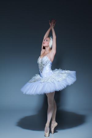 Portret van de ballerina in de rol van een witte zwaan op blauwe achtergrond Stockfoto