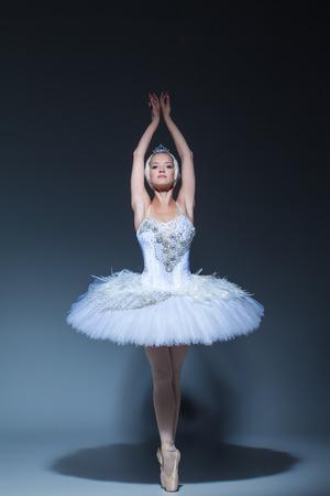 Portrait der Ballerina in der Rolle eines weißen Schwan auf blauem Hintergrund