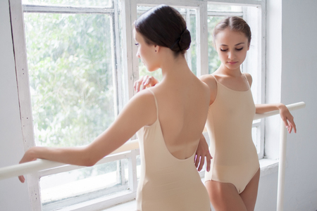 barre: The two classic ballet dancers posing at ballet barre on a  white room background Stock Photo
