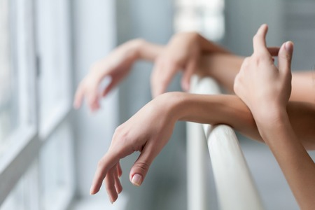 The hands of two classic ballet dancers at ballet barre on a  white room background Фото со стока