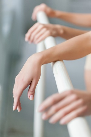 ballet bar: The hands of two classic ballet dancers at ballet barre on a  white room background Stock Photo