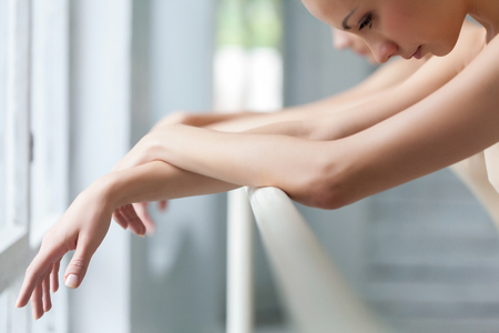 The hands of two classic ballet dancers at ballet barre on a  white room background Stock Photo