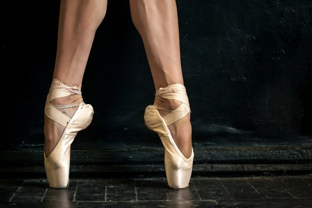 Close-up classic ballerinas legs in pointes on the black wooden floor Stock Photo