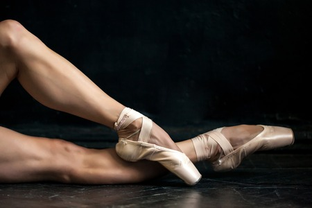 pointes: Close-up classic ballerinas legs in pointes on the black wooden floor Stock Photo