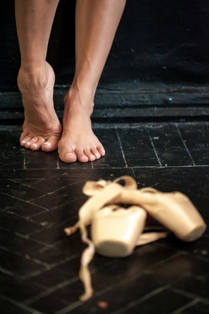 pointes: Close-up classic ballerinas legs and pointes on the black wooden floor Stock Photo