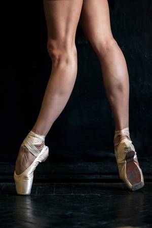pies bailando: Close-up classic ballerinas legs in pointes on the black wooden floor Foto de archivo