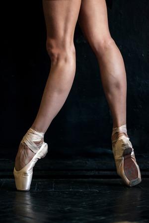 pies bailando: Primer plano las piernas de bailarina cl�sica en pointes en el piso de madera negro