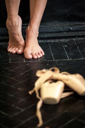 pies bailando: Close-up classic ballerinas legs and pointes on the black wooden floor Foto de archivo
