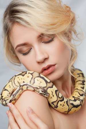 animal sexy: Beautiful blonde girl and python around her body on gray background Stock Photo