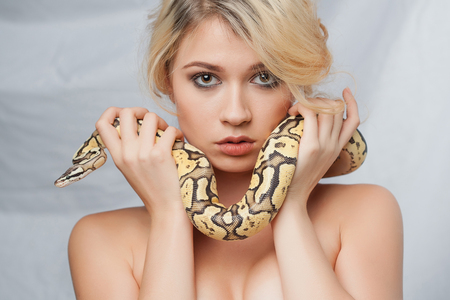 her: Beautiful blonde girl and python around her face on gray background