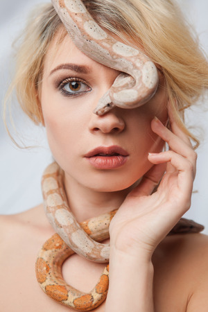 animal woman: Beautiful blonde girl and  the snake Boa constrictors around her face on gray background Stock Photo