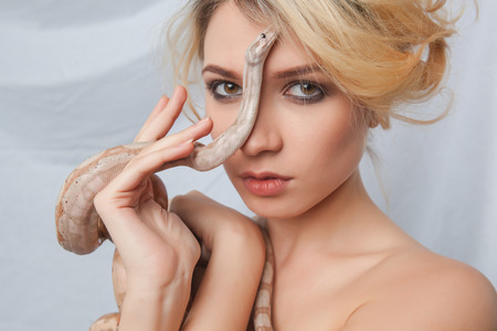 constrictors: Beautiful blonde girl and  the snake Boa constrictors around her face on gray background Stock Photo