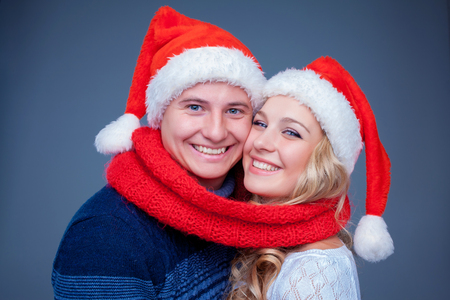 red scarf: Lovely christmas couple  in Santa Claus hats posing on blue background with red scarf