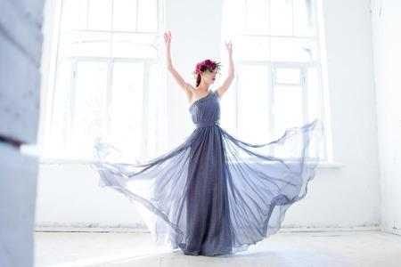models posing: La hermosa bailarina bailando en vestido gris largo en el fondo habitaci�n blanca