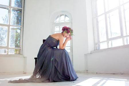 modelos posando: La hermosa bailarina sentada en vestido largo gris sobre fondo habitación blanca Foto de archivo