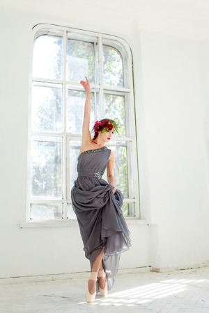 The beautiful ballerina dancing in long gray dress on white room background
