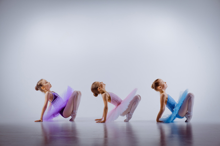 ballerina girl: Three little ballet girls sitting  in multicolored tutus and pointe shoes together on white background