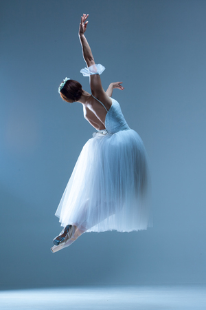Portrait of the jumping classical ballerina  in white dress on blue background