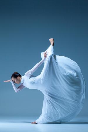 danseuse: Portrait de la ballerine contemporaine en robe blanche sur fond bleu