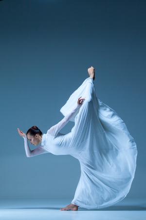 Portrait des modernen Ballerina in weißen Kleid auf blauem Hintergrund