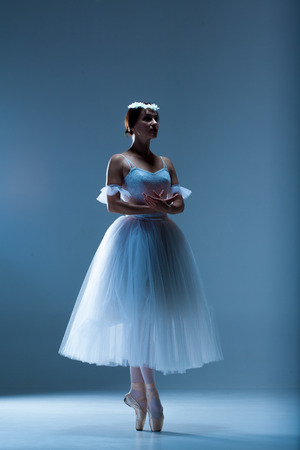 ballerina shoes: Portrait of the classical ballerina  in white dress on blue background