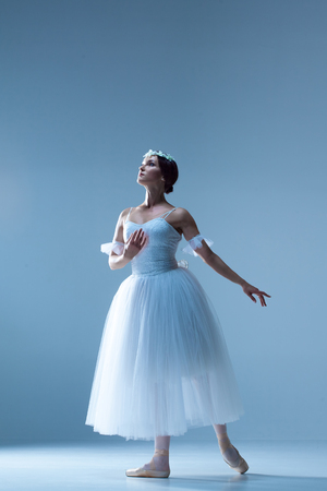 girl dress: Portrait of the classical ballerina  in white dress on blue background