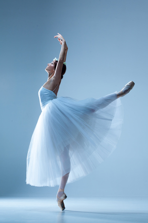 Portrait of the classical ballerina  in white dress on blue background