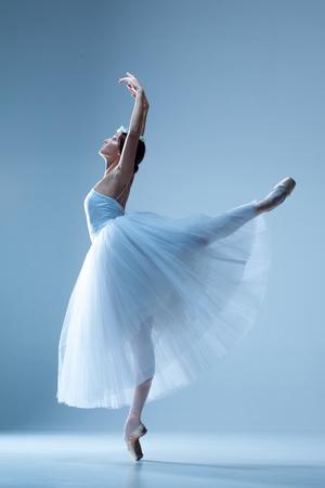 Portret van de klassieke ballerina in witte jurk op een blauwe achtergrond