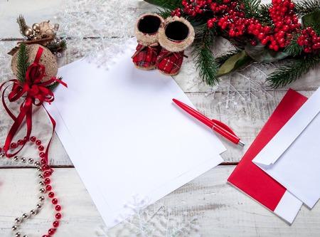 hoja en blanco: La hoja de papel en blanco sobre la mesa de madera con un lápiz y adornos navideños. Concepto maqueta de Navidad