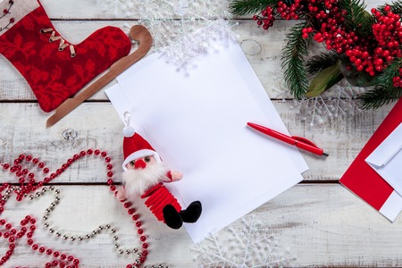 person writing: The blank sheet of paper on the wooden table with a pen and  Christmas decorations. Christmas mockup concept