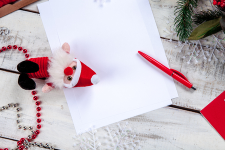 make a gift: The blank sheet of paper on the wooden table with a pen and  Christmas decorations. Christmas mockup concept