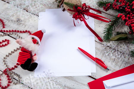 The blank sheet of paper on the wooden table with a pen and  Santa. Christmas mockup concept