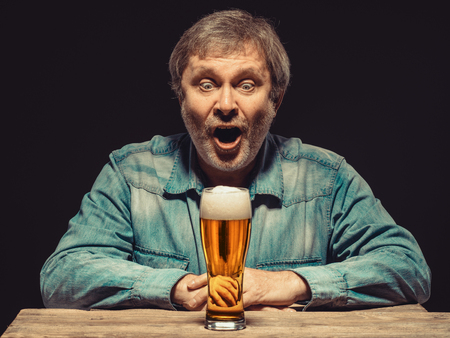 ecstasy: Enjoying his favorite beer.  The front view of handsome screaming man as fan in denim shirt with glass of beer, sitting at the wooden table. Concept of enthusiasm and ecstasy