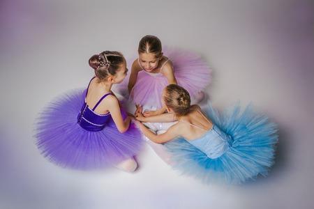 Tres niñas de ballet que se sientan en los zapatos del pointe tutus y multicolores juntos sobre fondo lila