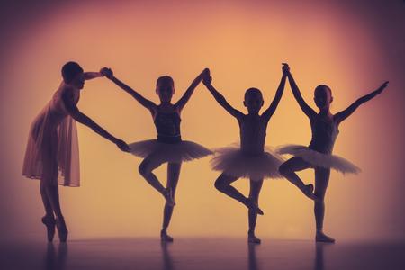 De silhouetten van de kleine ballerina's met persoonlijke ballet leraar in dansstudio poseren op een oranje achtergrond