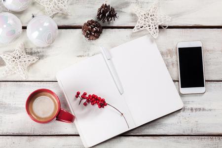 adviento: El cuaderno abierto sobre la mesa de madera con un teléfono y decoraciones de Navidad. Concepto maqueta de Navidad