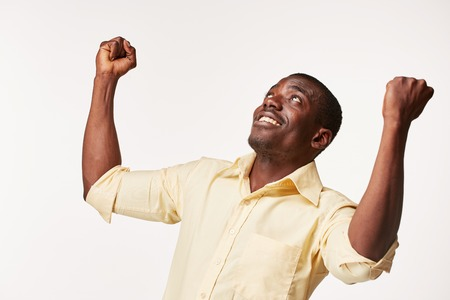 winner man: portrait of handsome young black african smiling man   on white background. human emotions - surprise. face close up Stock Photo
