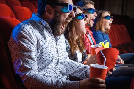 Een verscheidenheid van de menselijke emoties van vrienden met een cola en popcorn in de bioscoop.