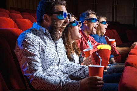 Una variedad de emociones humanas de amigos la celebración de un refresco de cola y palomitas en el cine.