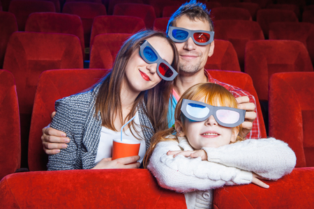 spectators: The spectators sitting in the cinema and watching movie  with cup of cola. Concept of a variety of human emotions. Stock Photo