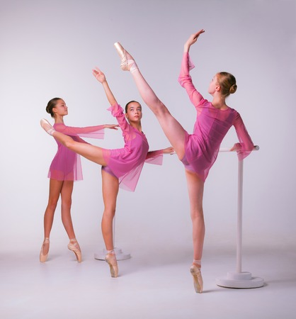 Three young ballerinas stretching on the bar on beige background