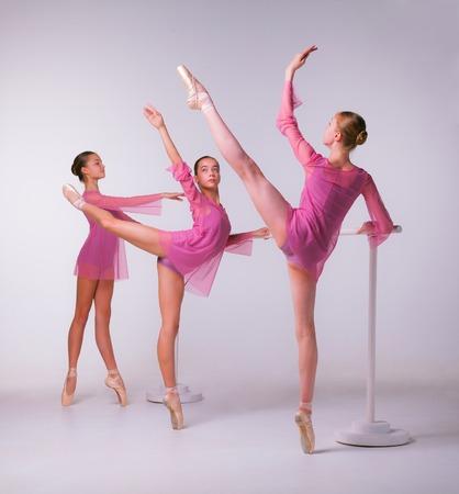 ballet niñas: Tres bailarinas jóvenes se extiende en el bar en el fondo de color beige Foto de archivo