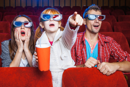 The spectators sitting in the cinema and watching movie  with cups of cola. Concept of a variety of human emotions.
