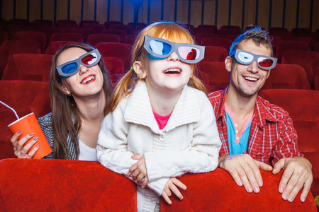 cinema people: The spectators sitting in the cinema and watching movie  with cups of cola. Concept of a variety of human emotions.