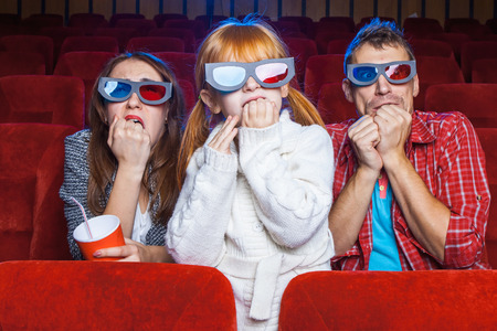spectators: The spectators sitting in the cinema and watching movie  with cups of cola. Concept of a variety of human emotions.