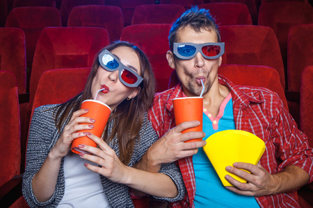 The spectators sitting in the cinema and watching movie  with cups of cola and popcorn. Concept of a variety of human emotions. Stock Photo - 48474928