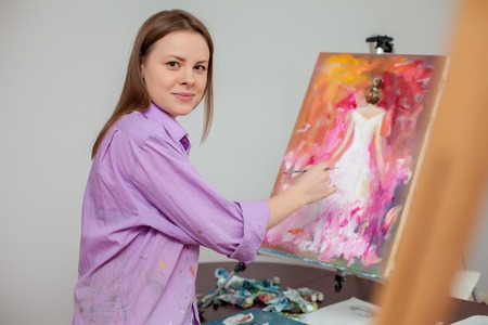 portrait young girl studio: Creative female artist  drawing the picture in the studio