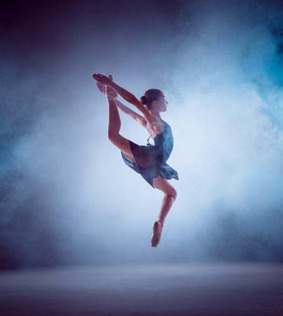 gir: The silhouette of young ballerina jumping on a blue background.