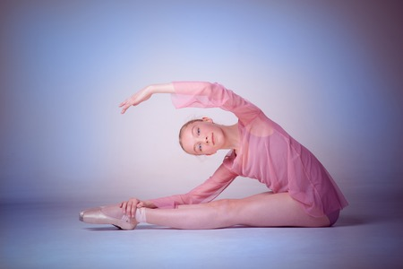 flexable: The  young ballerina  posing on the floor on lilac background Stock Photo