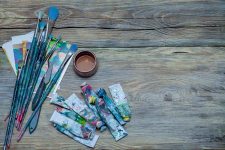 De hulpmiddelen van de kunstenaar - verven en borstels op houten achtergrond Stockfoto